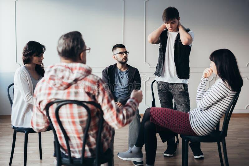 Reunión de la ayuda con el psiquiatra para los adictos en centro de rehabilitación fotografía de archivo