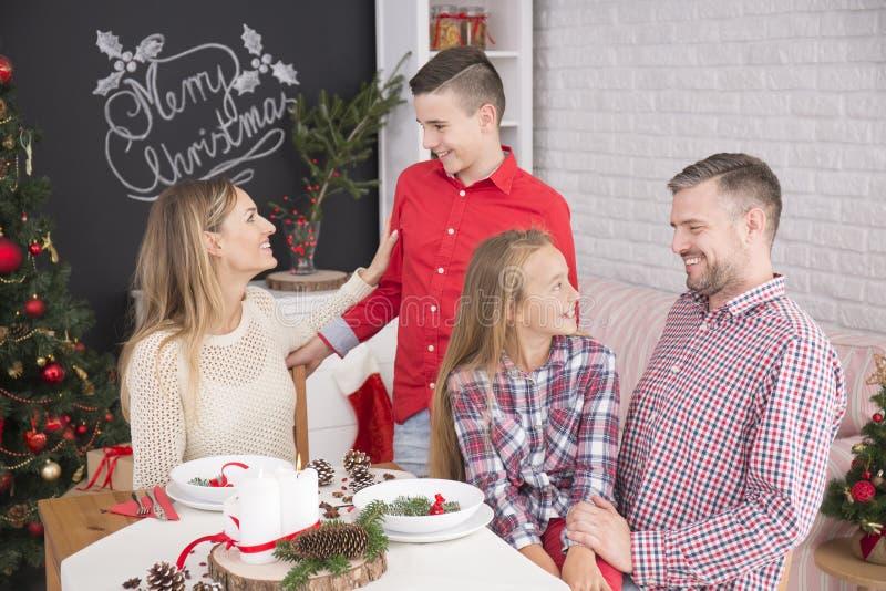 Reunión de la familia en la tabla de la Navidad imagen de archivo