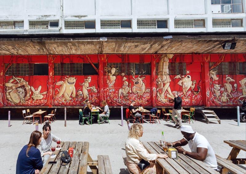 Reunión de la gente y bebidas de consumición en el restaurante al aire libre en área urbana de la ciudad con las tiendas y los ca foto de archivo libre de regalías