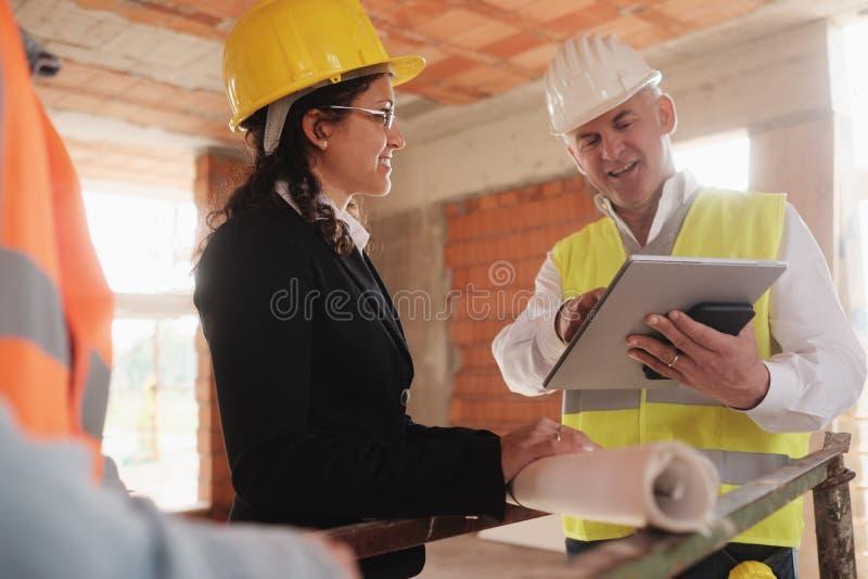 Reunión de And Manual Worker del ingeniero del arquitecto en emplazamiento de la obra imagen de archivo libre de regalías