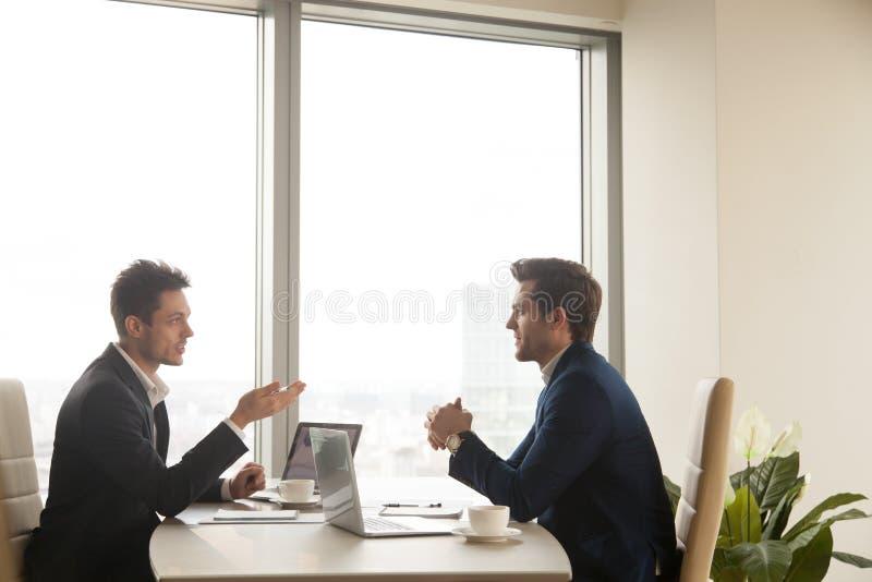 Reunión de negocios de dos socios que hablan y que trabajan en los ordenadores portátiles fotos de archivo