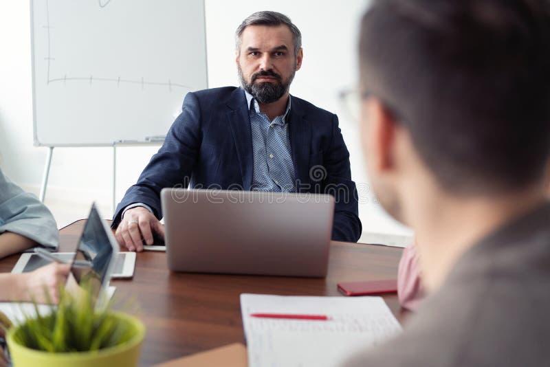 Reunión de negocios Dos hombres de negocios que se sientan delante de uno a en la oficina mientras que discute algo fotos de archivo libres de regalías