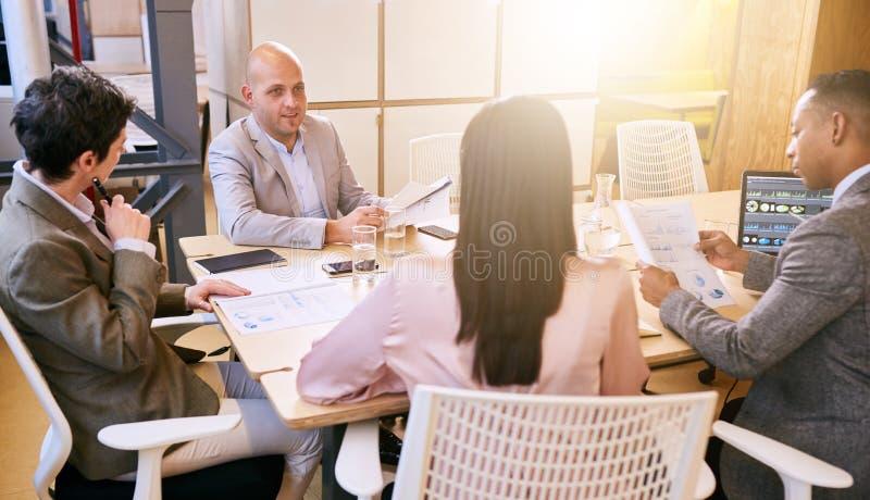 Reunión de negocios entre cuatro ejecutivos emprendedores profesionales dentro foto de archivo libre de regalías