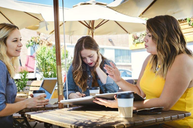 Reunión de negocios de la cafetería con 3 Millennials joven foto de archivo