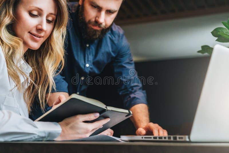 Reunión de negocios Trabajo en equipo Empresaria y hombre de negocios sonrientes que se sientan en la tabla delante del ordenador foto de archivo