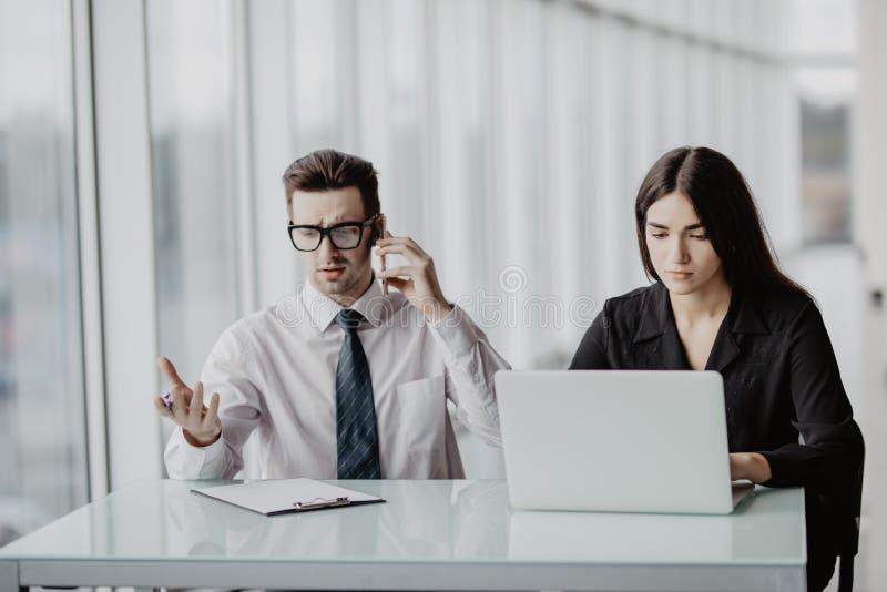 Reunión de reflexión creativa joven del equipo en la oficina Hombre de negocios masculino hermoso que hace llamada mientras que a fotos de archivo libres de regalías