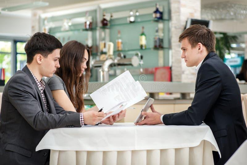 ¡Reunión de Specials! Hombre de negocios de tres jóvenes que asiste en una tabla fotografía de archivo libre de regalías