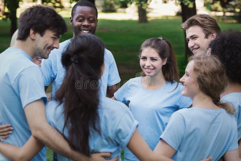 Reunión del equipo joven de los voluntarios en parque fotografía de archivo libre de regalías