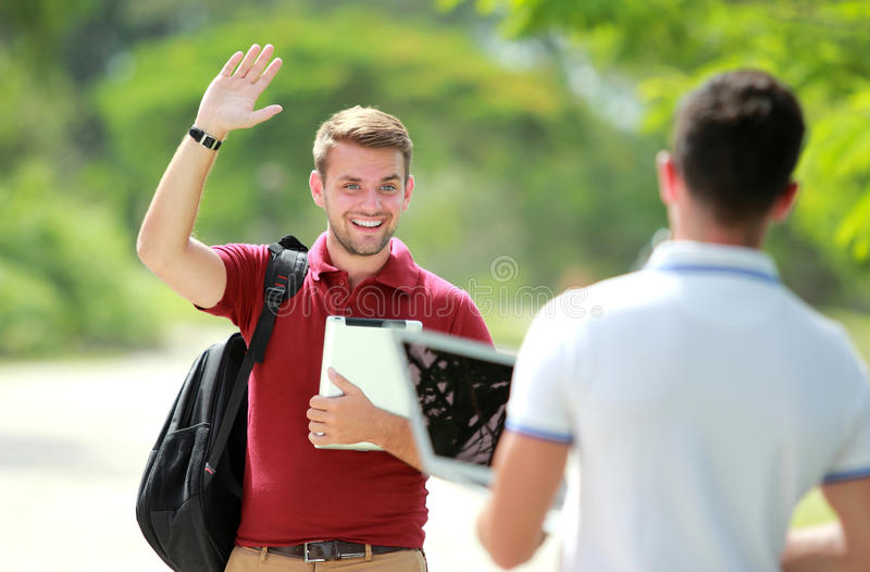 Reunión del estudiante universitario su amigo y agitar su mano fotos de archivo libres de regalías