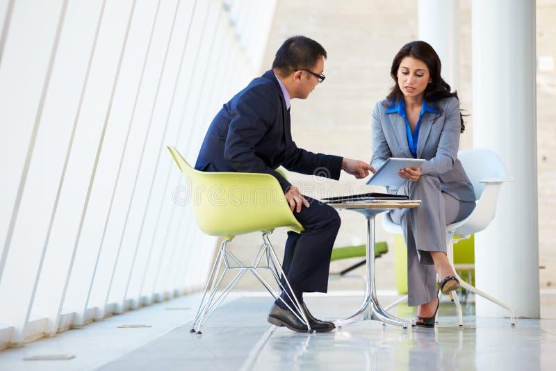 Reunión del hombre de negocios y de la empresaria en oficina moderna fotos de archivo