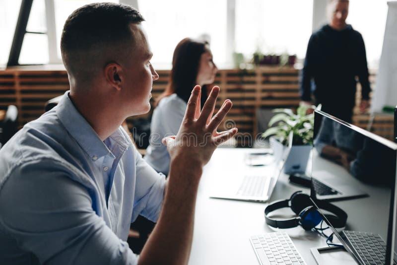 Reunión del personal de un equipo acertado joven en la oficina moderna ligera equipada del mobiliario de oficinas moderno foto de archivo libre de regalías
