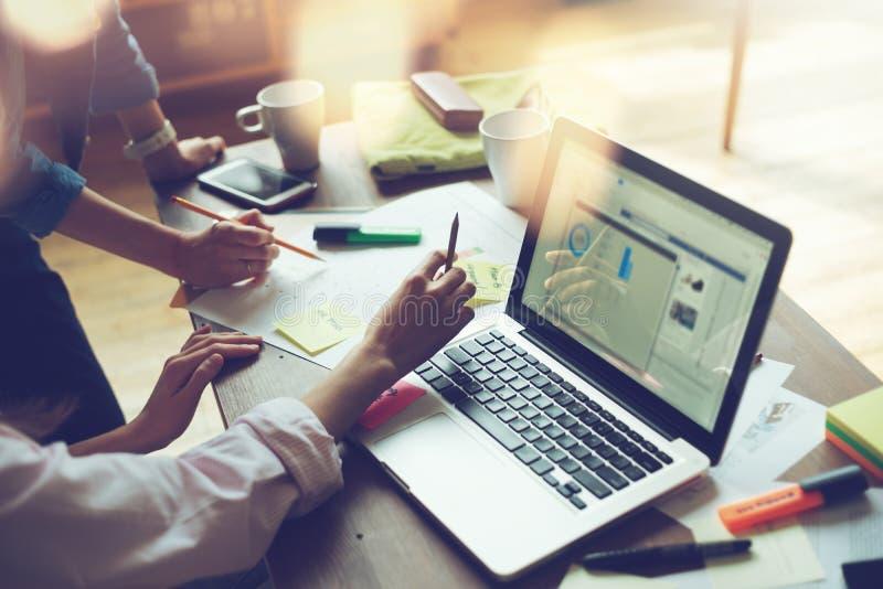 Reunión del proyecto del negocio Equipo de comercialización que discute nuevo plan de funcionamiento Ordenador portátil y papeleo foto de archivo