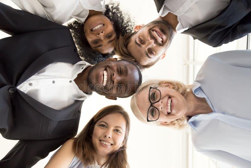 Reunión diversa feliz del equipo del negocio en el círculo que mira el camer imagen de archivo