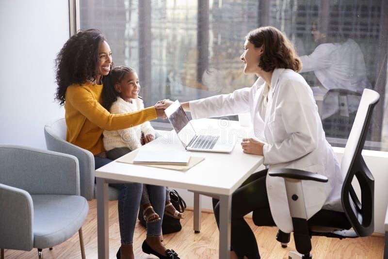 Reunión femenina de la madre y de la hija de Shaking Hands With del pediatra en oficina del hospital fotos de archivo libres de regalías