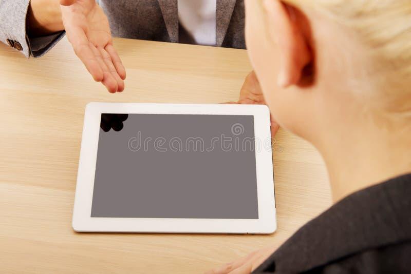 Reunión-hombre del negocio que muestra algo en la tableta imagenes de archivo