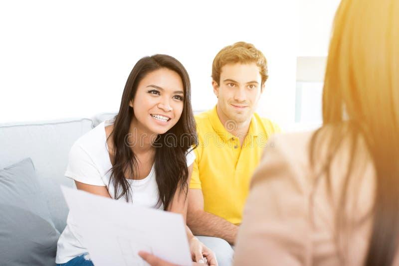Reunión interracial joven de los pares con el consultor imagenes de archivo