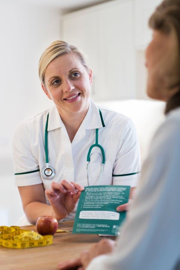Reunión madura de la mujer con el dietético en los doctores Office imagen de archivo libre de regalías