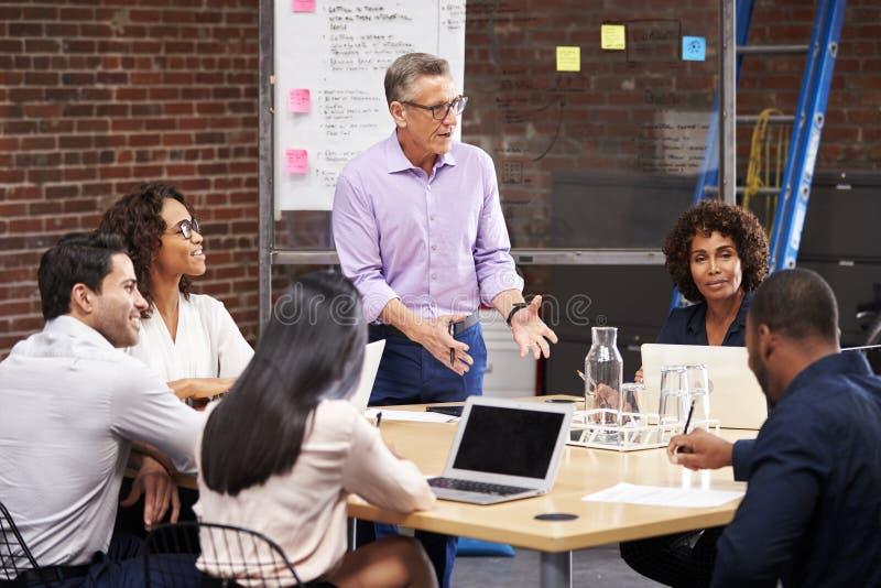 Reunión madura de la oficina de Standing And Leading del hombre de negocios de los colegas que se sientan alrededor de la tabla imagen de archivo