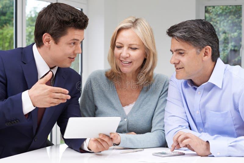 Reunión madura de los pares con el consejero financiero en casa foto de archivo
