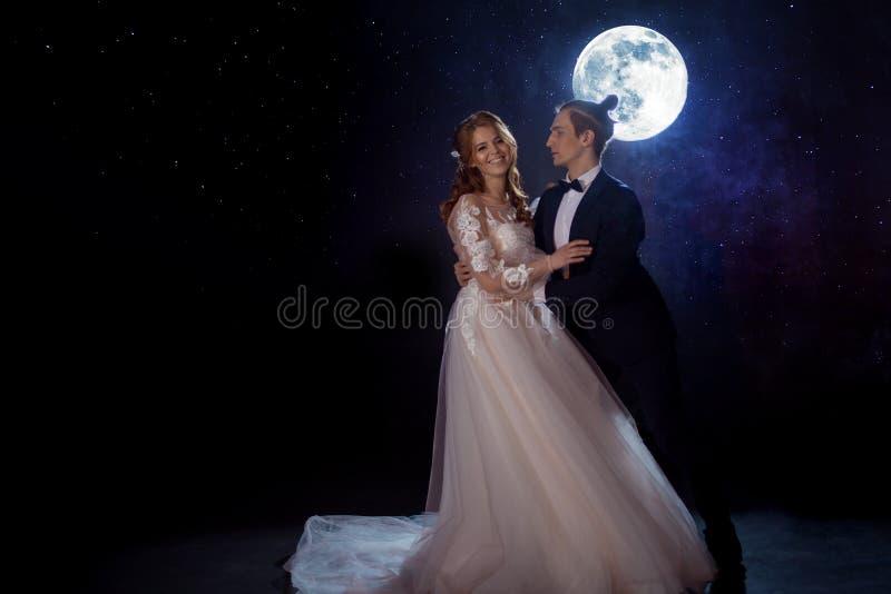 Reunión misteriosa y romántica, la novia y novio debajo de la luna Abrazos junto Técnicas mixtas foto de archivo libre de regalías