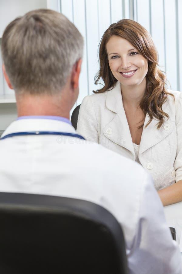 Reunión paciente de la mujer feliz con el doctor de sexo masculino en oficina imagen de archivo libre de regalías