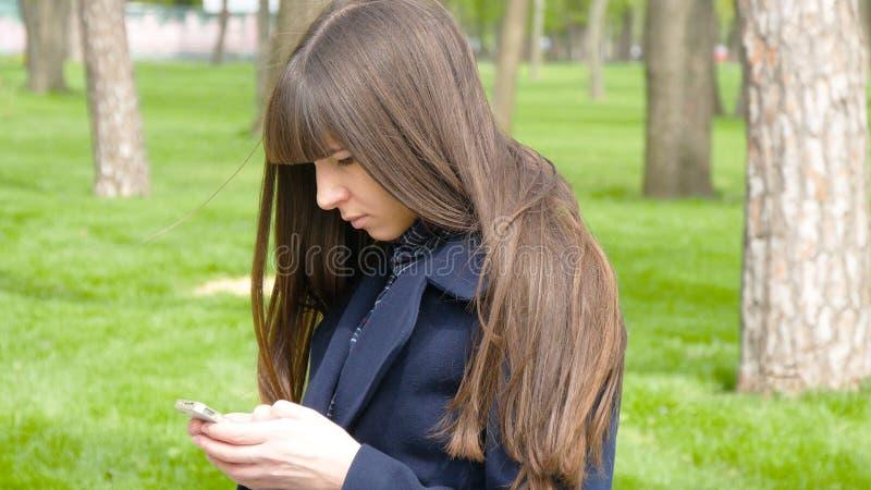 Reunión que espera en el parque - detalle de la mujer hermosa para Ella que mira alrededor y teléfono elegante mibile de las apli fotos de archivo libres de regalías