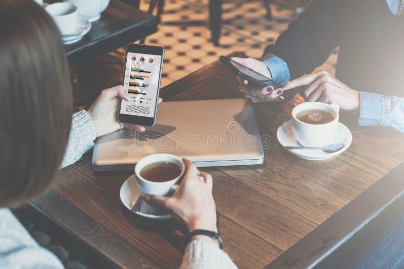 Reunión unívoca Mujer que mira en gráficos, cartas y diagramas en la pantalla del smartphone fotos de archivo