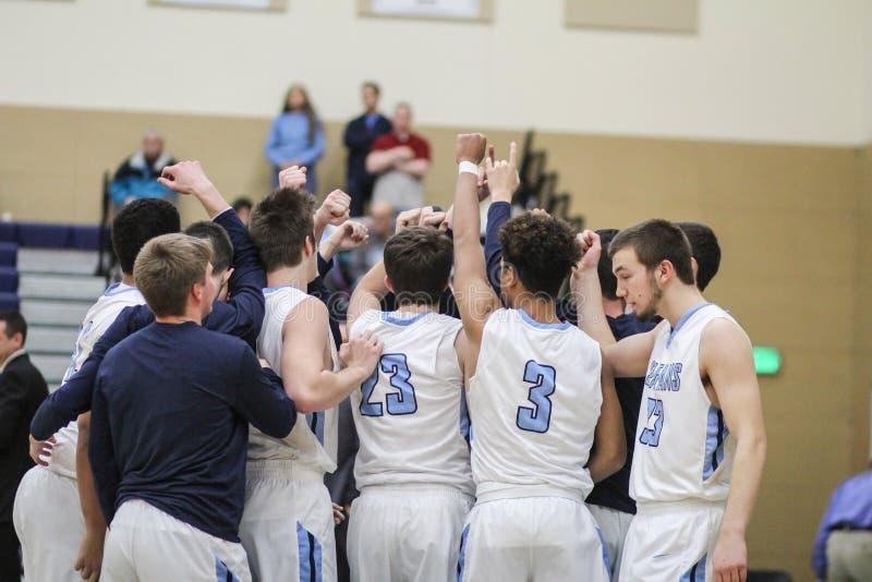 Reuniões da equipa de basquetebol dos meninos antes do começo do jogo foto de stock