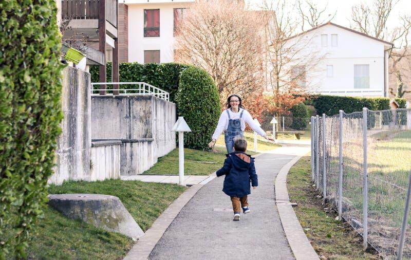 Reuni?n de la hermana y del hermano Muchacha feliz del tween que corre hacia su pequeño hermano con sus brazos abiertos fotos de archivo