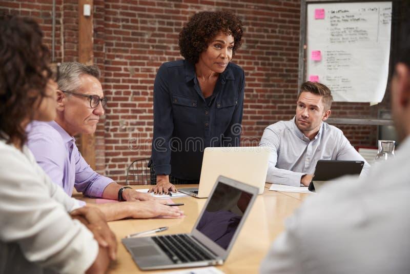 Reuni?n madura de la oficina de Standing And Leading de la empresaria alrededor de la tabla imagen de archivo