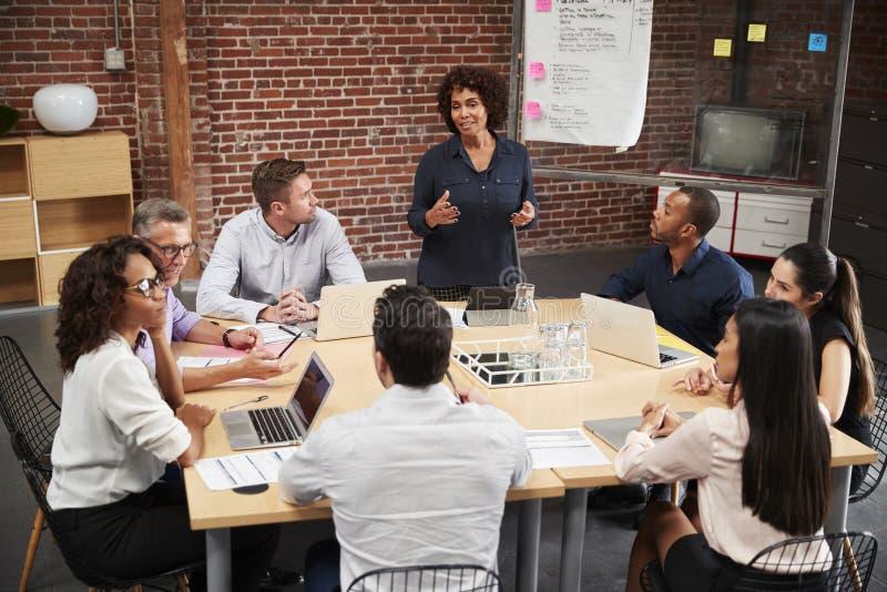 Reuni?n madura de la oficina de Standing And Leading de la empresaria alrededor de la tabla fotos de archivo