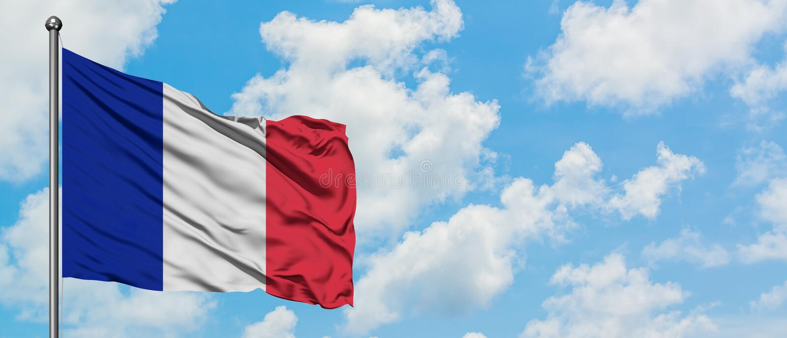 Reunion flag waving in the wind against white cloudy blue sky. Diplomacy concept, international relations.  royalty free stock image