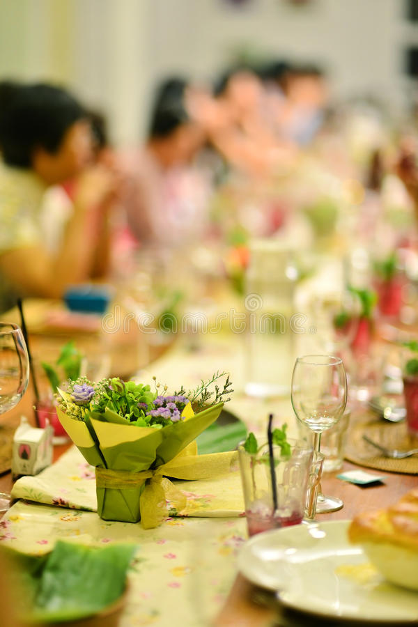 Reunion party. In warm ambient , focus on the flower bouquet on dining table stock images