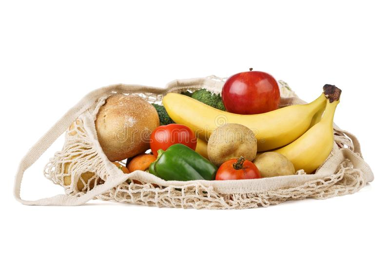 Reusable eco-friendly strip shopping bag full of various food. Fruits, vegetables and bread. Isolated on white background, string, grocery, textile, mesh royalty free stock photo