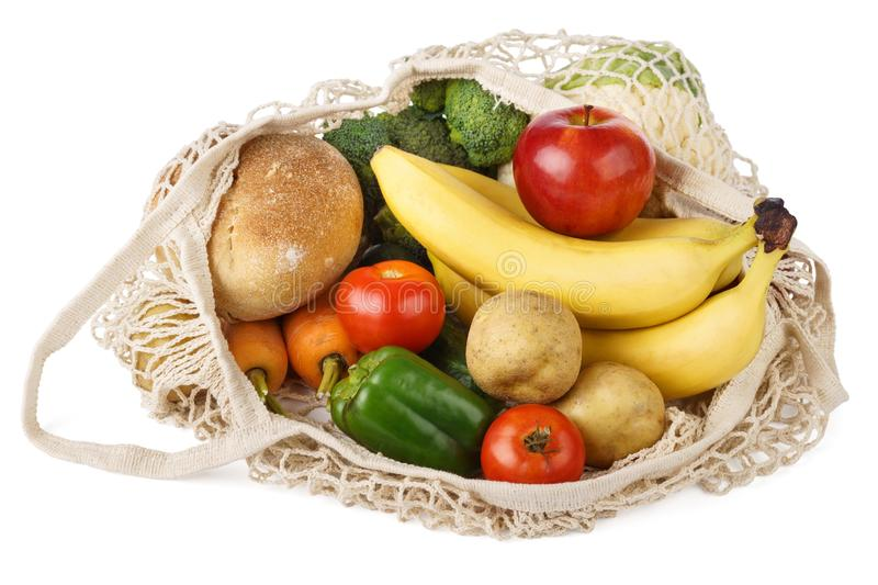Reusable eco-friendly strip shopping bag full of various food. Fruits, vegetables and bread. Isolated on white background, string, grocery, textile, mesh stock photography