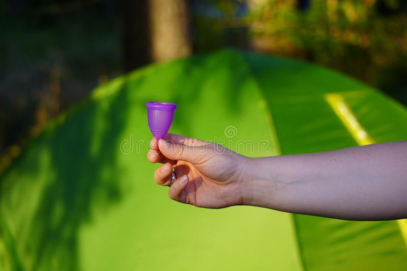 Reusable Menstrual Cup on vacation, camping, during outdoor activities. convenience, environmental friendliness, zero waste. The reusable Menstrual Cup on royalty free stock photo