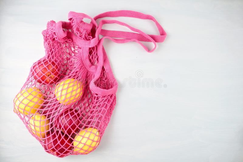 Reusable shopping mesh bag with lemons, fruits and glass bottle. Zero waste, plastic free concept. Summer refreshing food stock photo