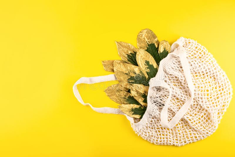 Reusable shopping net bag with green and golden leaves on yellow fall autumn background. Top view of eco friendly mesh shopping. Cotton bag. Ecological, Zero royalty free stock images