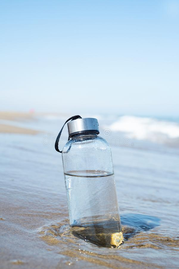 Reusable water bottle on the beach. Closeup of a glass reusable water bottle on the seashore of a lonely beach royalty free stock image