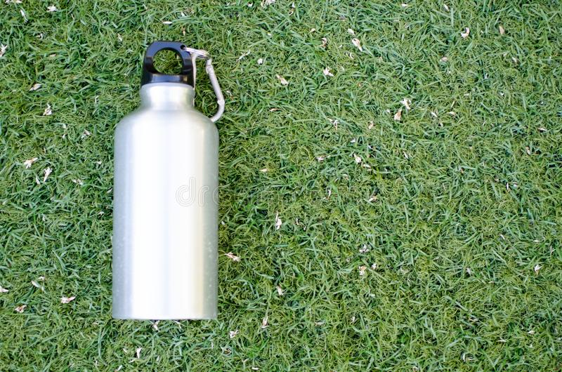 Reusable water bottle. On a green grass background stock images