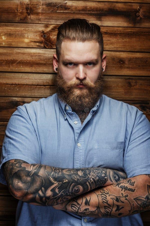 Reusachtig mannetje met baard en tatoegeringen stock afbeelding