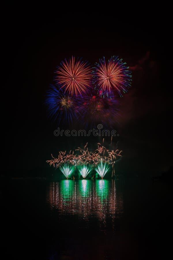 Reusachtig, rijk en kleurrijk vuurwerk over oppervlakte van Brno Dam met bezinning over de oppervlakte van meer royalty-vrije stock afbeelding