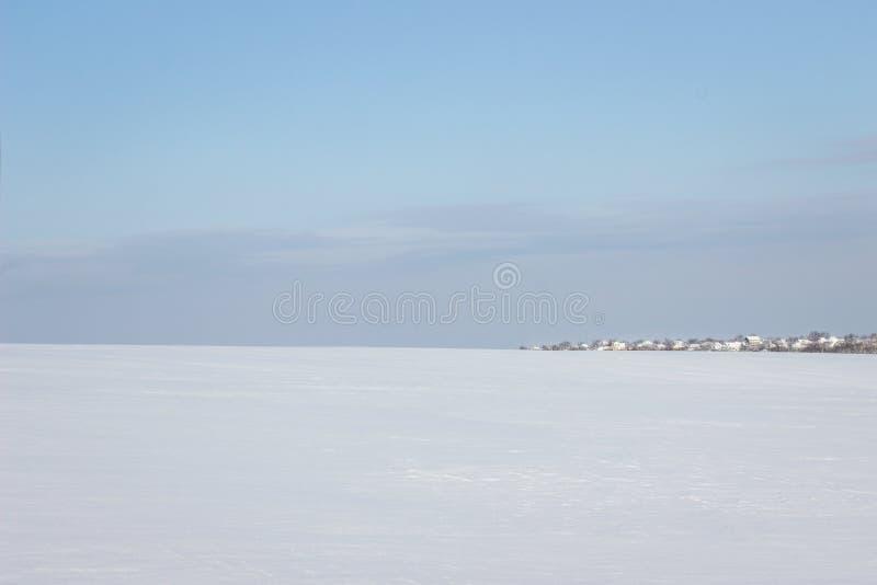 Reusachtig sneeuw behandeld gebied die tot het dorp onder de blauwe hemel leiden royalty-vrije stock foto