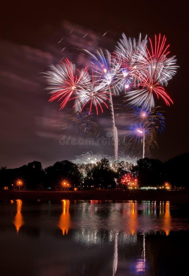 Reusachtig vuurwerk met bezinning in het meer stock fotografie