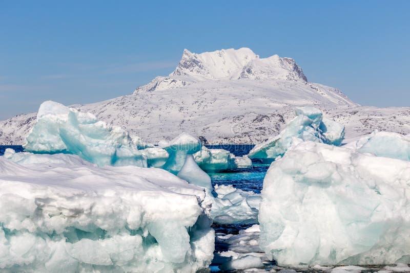 Reusachtige blauwe en ijsbergen die, Groenland aan wal afdrijven leggen royalty-vrije stock foto