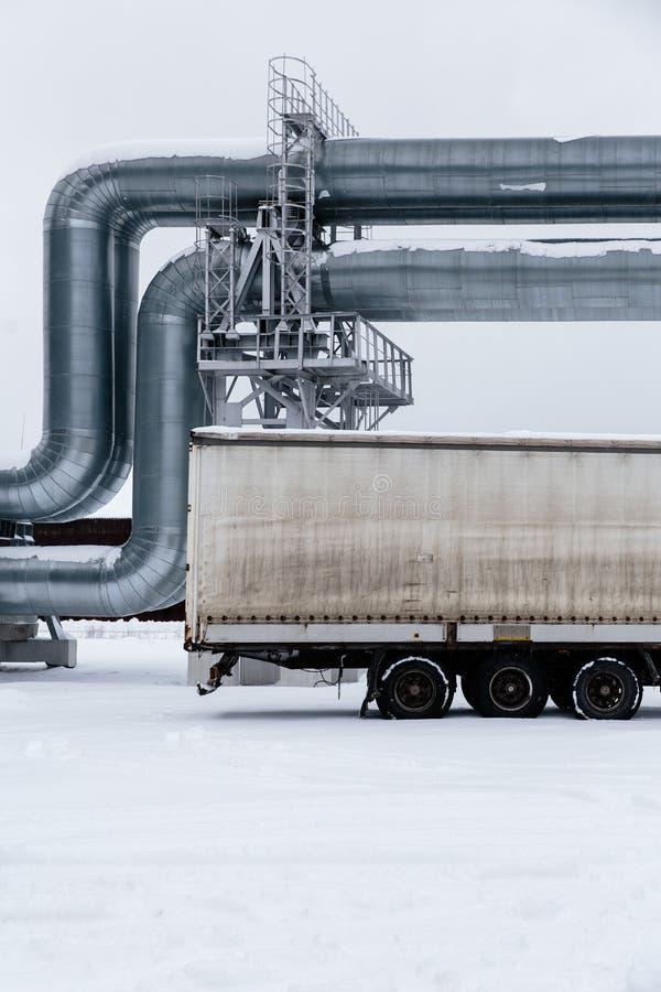 Reusachtige die aardgasleiding langs sneeuwstraat in Riga, Letland wordt gelegd stock fotografie
