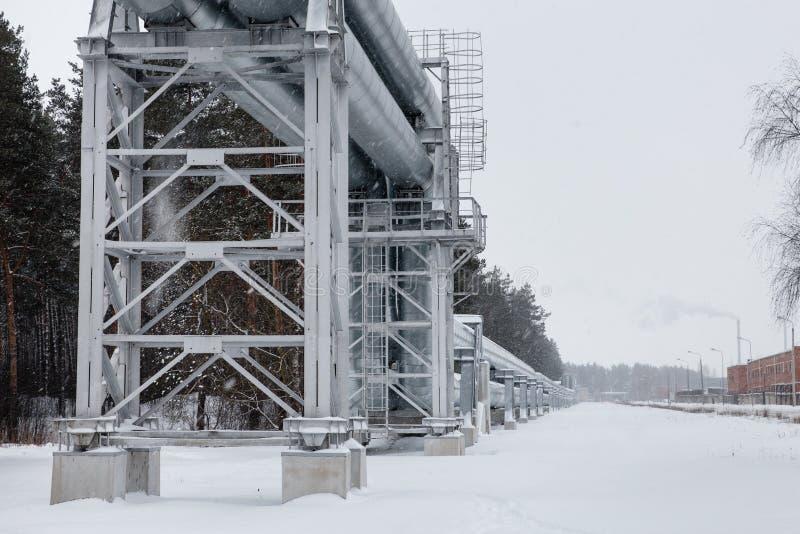 Reusachtige die aardgasleiding langs sneeuwstraat in Riga, Letland wordt gelegd royalty-vrije stock foto
