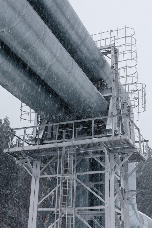 Reusachtige die aardgasleiding langs sneeuwstraat in Riga, Letland wordt gelegd stock foto