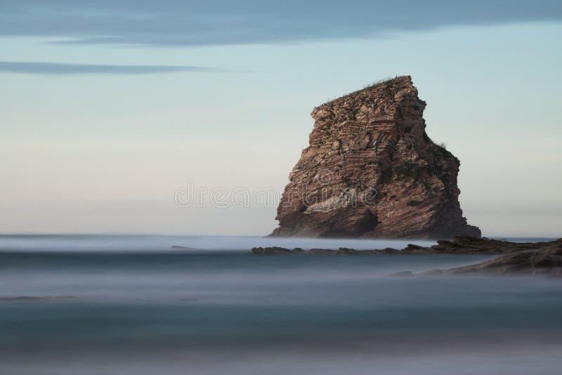 Reusachtige die rotsklip in oceaan in lange blootstelling in zonsonderganghemel wordt geïsoleerd, hendaye, Baskisch land, Frankri royalty-vrije stock foto's