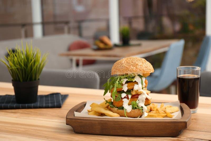 Reusachtige die yummy hamburger op lijst in koffie wordt gediend stock foto